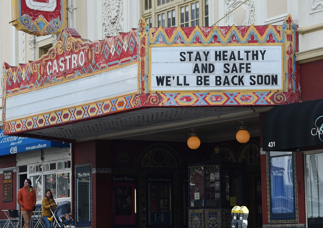 A couple walks by the Castro theater with their baby in San Francisco, California on 17 March 2020. (Josh Edelson/AFP)