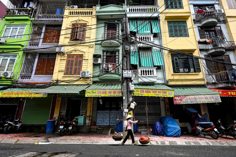 """This photograph taken on 8 June 2021 shows a street vendor walking past narrow residential houses, known as """"nha ong"""" in Vietnamese or """"tube houses"""", in an urban area of Hanoi. (Manan Vatsyayana/AFP)"""