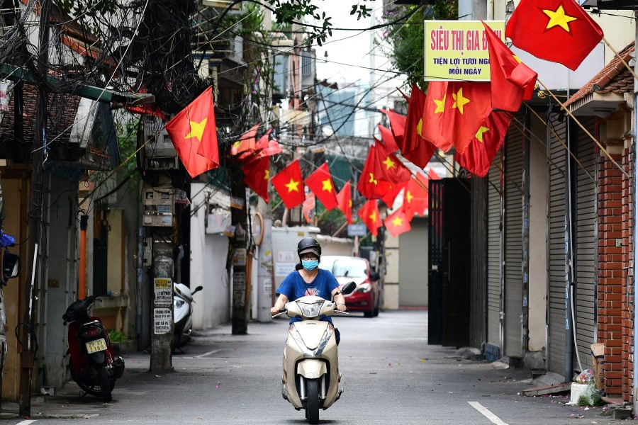 A woman rides a scooter along a street decorated with Vietnamese national flags ahead of Vietnam's National Day celebrations in Hanoi on 1 September 2021. (Nhac Nguyen/AFP)