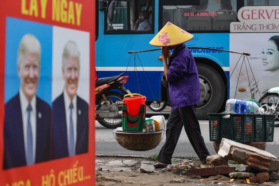 A street vendor walks past a billboard for a photo studio featuring an image of US President Donald Trump in Hanoi, 24 November 2020. (Nhac Nguyen/AFP)