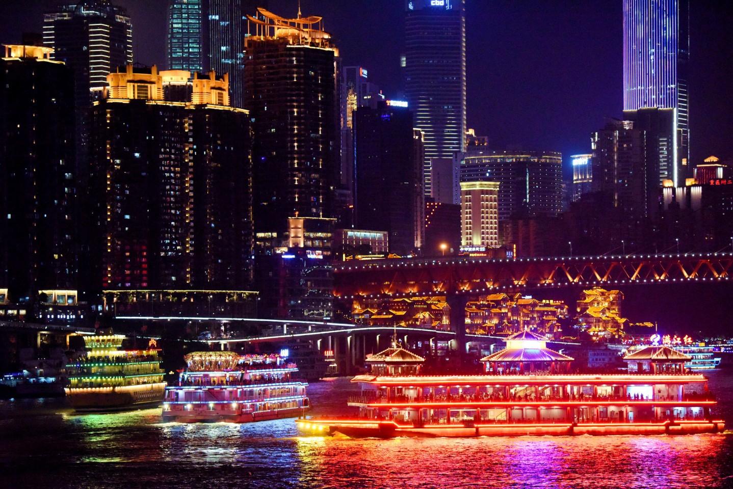 Chongqing's beautiful city skyline by night. A cruise ship is seen passing by Hongyadong. (Xinhua)