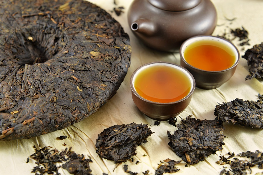 A pu-erh cake and cups of pu-erh tea. (iStock)