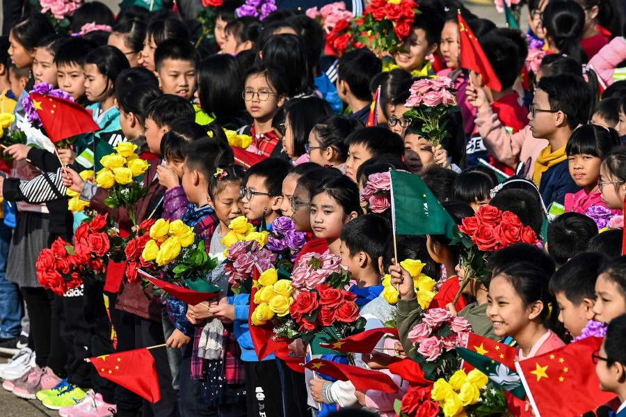 """The Chinese system has governance capacity to tackle the emerging """"troubled times"""". This picture shows children waiting to bid farewell to China's President Xi Jinping and his wife Peng Liyuan at the international airport in Macau on 20 December, 2019.  (Photo by Eduardo Leal/AFP)"""