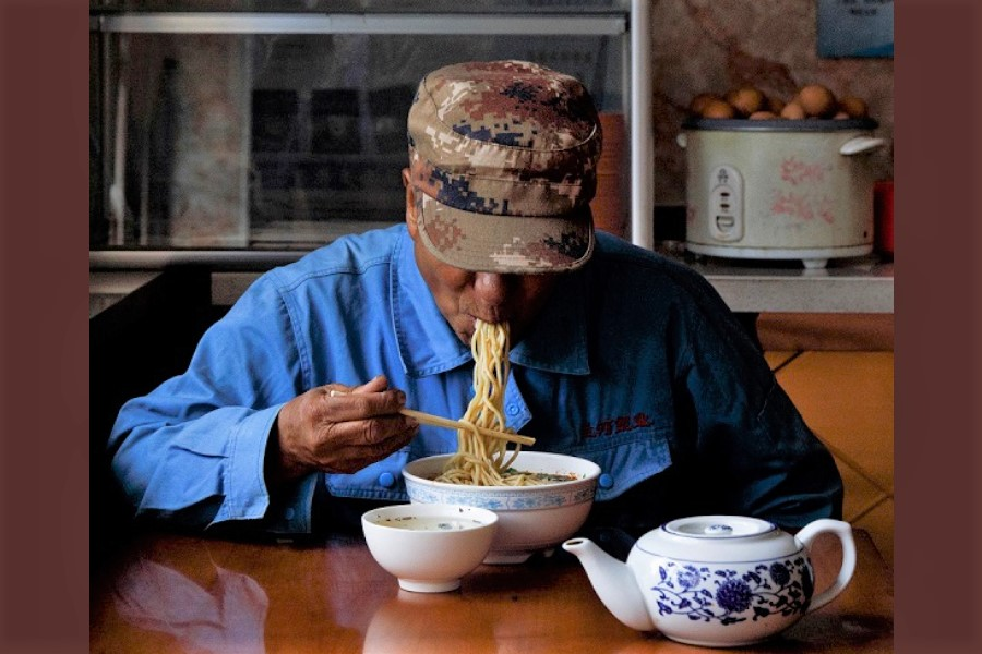 A man eats Lanzhou-style noodles at a restaurant that once served workers of the now decommissioned Liancheng coal-fired power plant in Heqiao village, Yongdeng county, Gansu province, China, 16 September 2020. (Thomas Peter/Reuters)