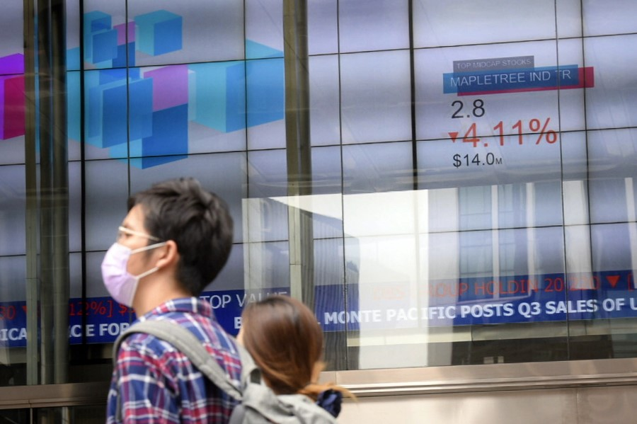 People pass an electronic stock board at The SGX Centre on 12 March, 2020. (SPH)
