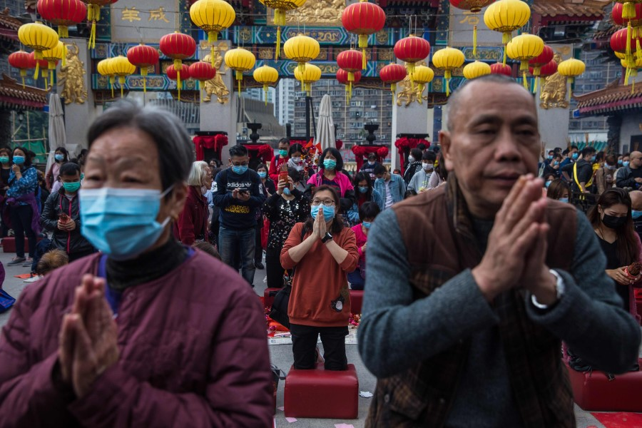 Visitors offer up prayers on the first day of the first lunar month at Wong Tai Sin temple in Hong Kong, 25 January 2020. (Dale de la Rey/AFP)