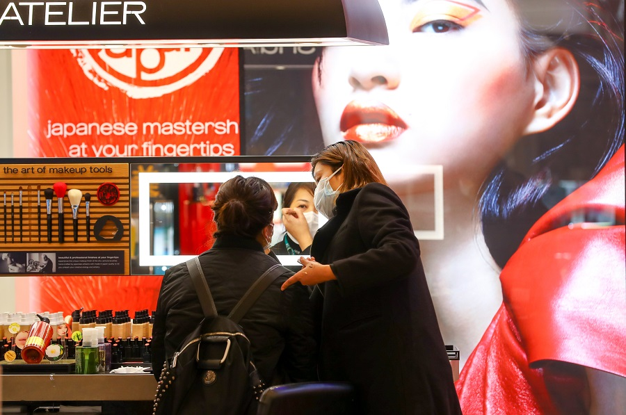 In this photo taken on 30 March, a sales assistant helps a consumer try-on makeup products, as shopping malls in Wuhan are gradually reopening. (CNS)