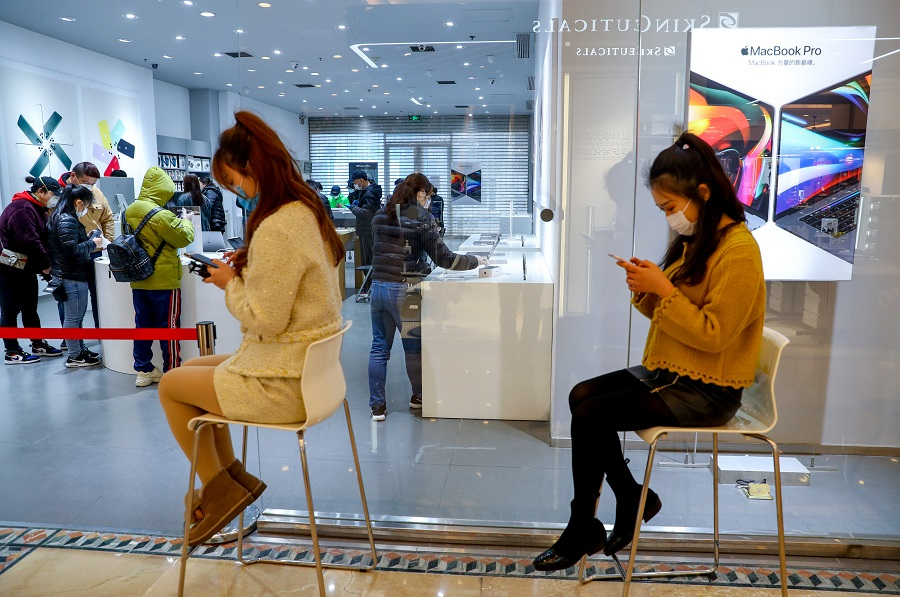 In this photo taken on 30 March, customers line up to enter a mobile phone shop in Wuhan after shopping malls resumed operations. (CNS)