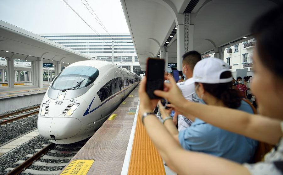 People take photos on the platform as a train arrives at Zigong Railway Station in Sichuan, China, on 28 June 2021, the first day of its operations. (CNS)