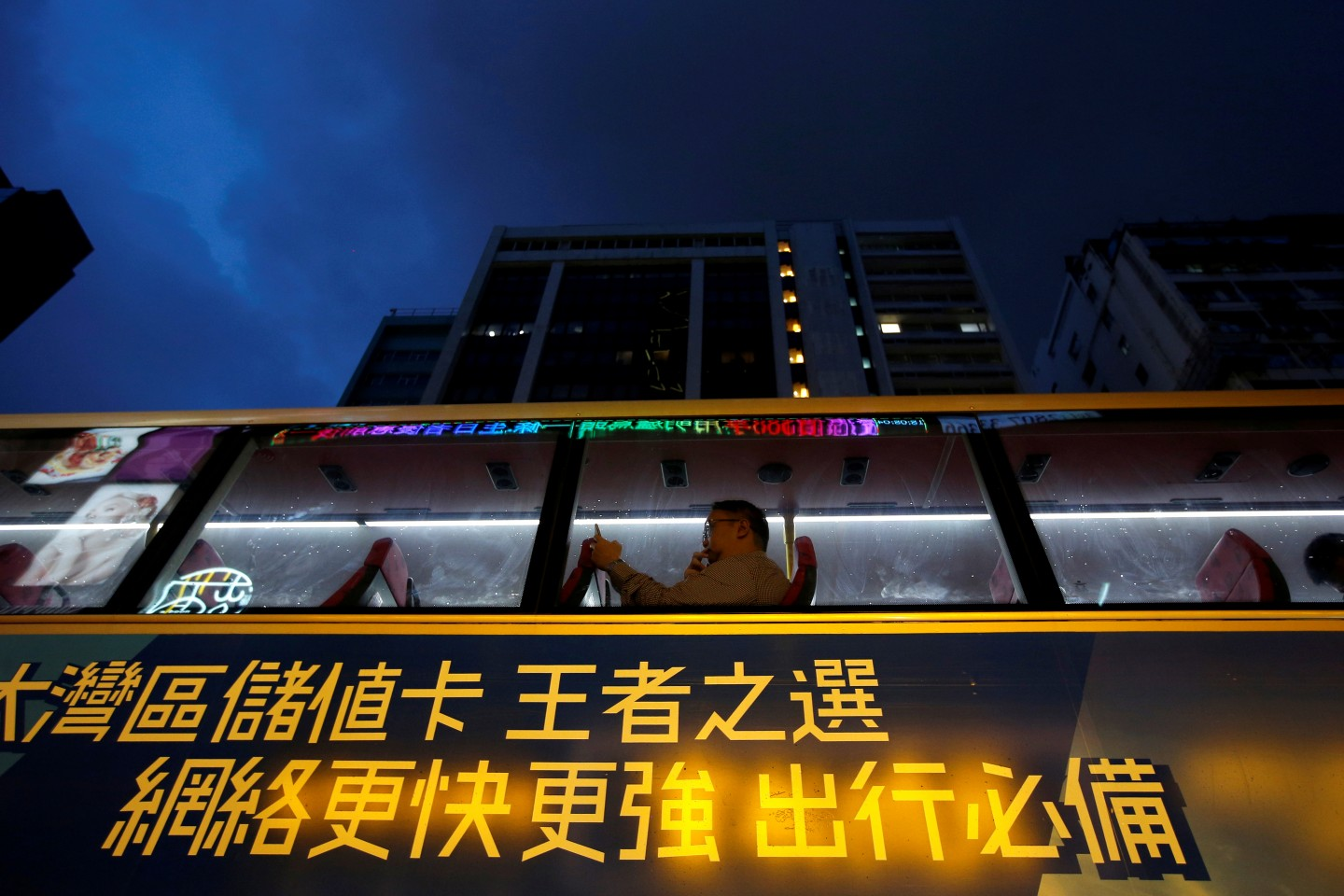 A man uses a phone as he travels on a bus with an advertisement for Greater Bay area SIM cards, in Hong Kong, China, August 19, 2019. REUTERS/Willy Kurniawan/File Photo
