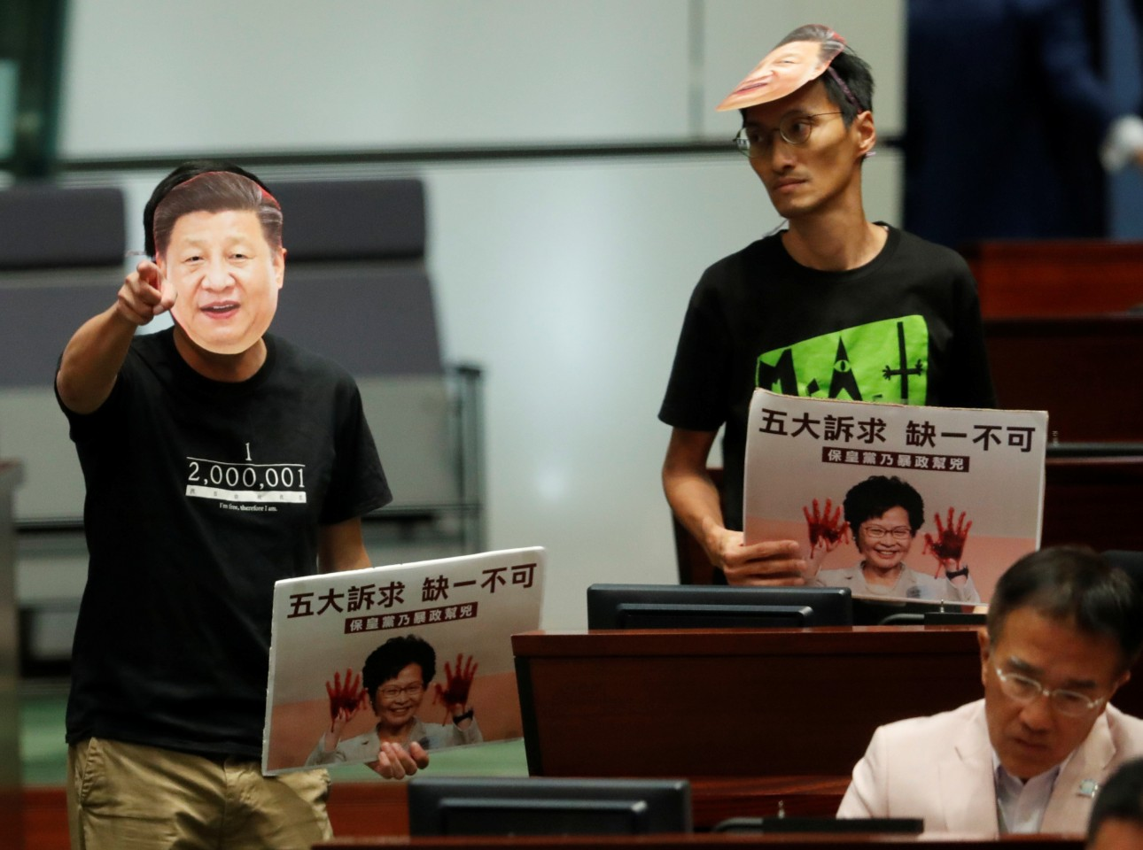 The impression that the Hong Kongers have of the central government and the mainland is directly related to the LOCPG's work. In the photo, a lawmaker in a mask depicting Chinese President Xi Jinping protests as Hong Kong Chief Executive Carrie Lam attempts to deliver her annual policy address at the Legislative Council in Hong Kong on October 16, 2019. (Kim Kyung-Hoon/Reuters)