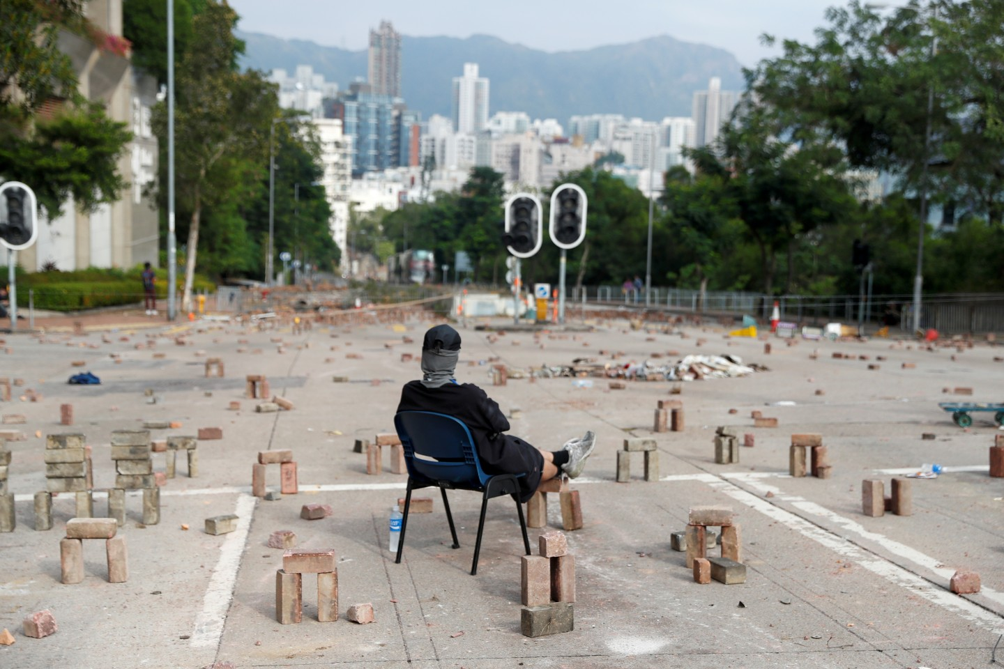 A protester sits amid a road block outside City University in Kowloon Tong on November 12, 2019. (REUTERS/Thomas Peter)