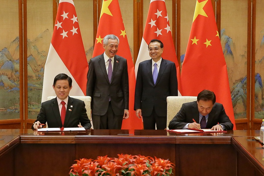 Singapore Prime Minister Lee Hsien Loong (standing, left) and Chinese Premier Li Keqiang (standing, right) witnessing the MOU-signing at the Diaoyutai State Guesthouse in Beijing on 29 April 2019. Representing Singapore is Minister of Trade and Industry Mr Chan Chun Sing (sitting, left) and China's National Development and Reform Commission Vice-Chair Zhang Yong. (SPH)