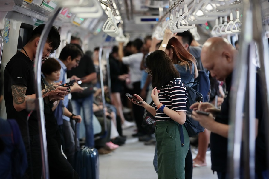 Commuters in the MRT train using their smartphones as they commute in Singapore on 17 October 2019. (SPH)