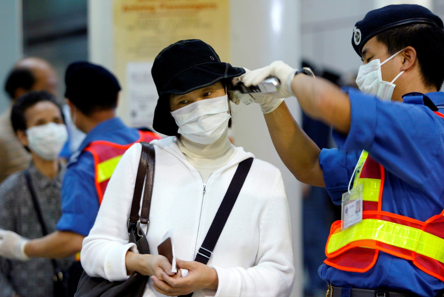 In this file photo, a health worker wearing a mask to protect from SARS takes a woman's temperature, after she arrived in Hong Kong by train from Guangzhou, on 24 April 2003. (Kin Cheung/File Photo/Reuters)