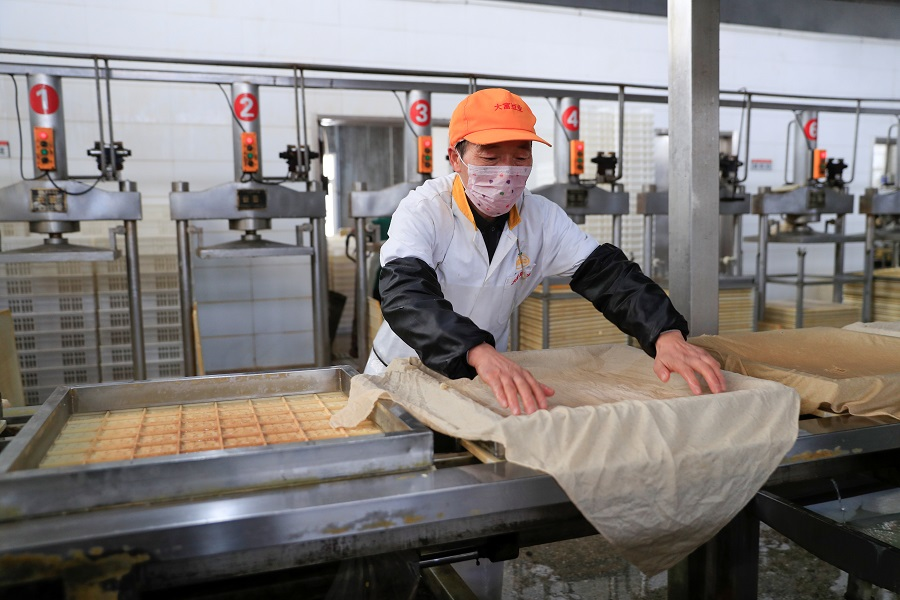 A worker wearing a face mask works on a production line manufacturing soybean-based food products at a factory in Hefei, Anhui, China, on 4 February 2020. (China Daily via Reuters)