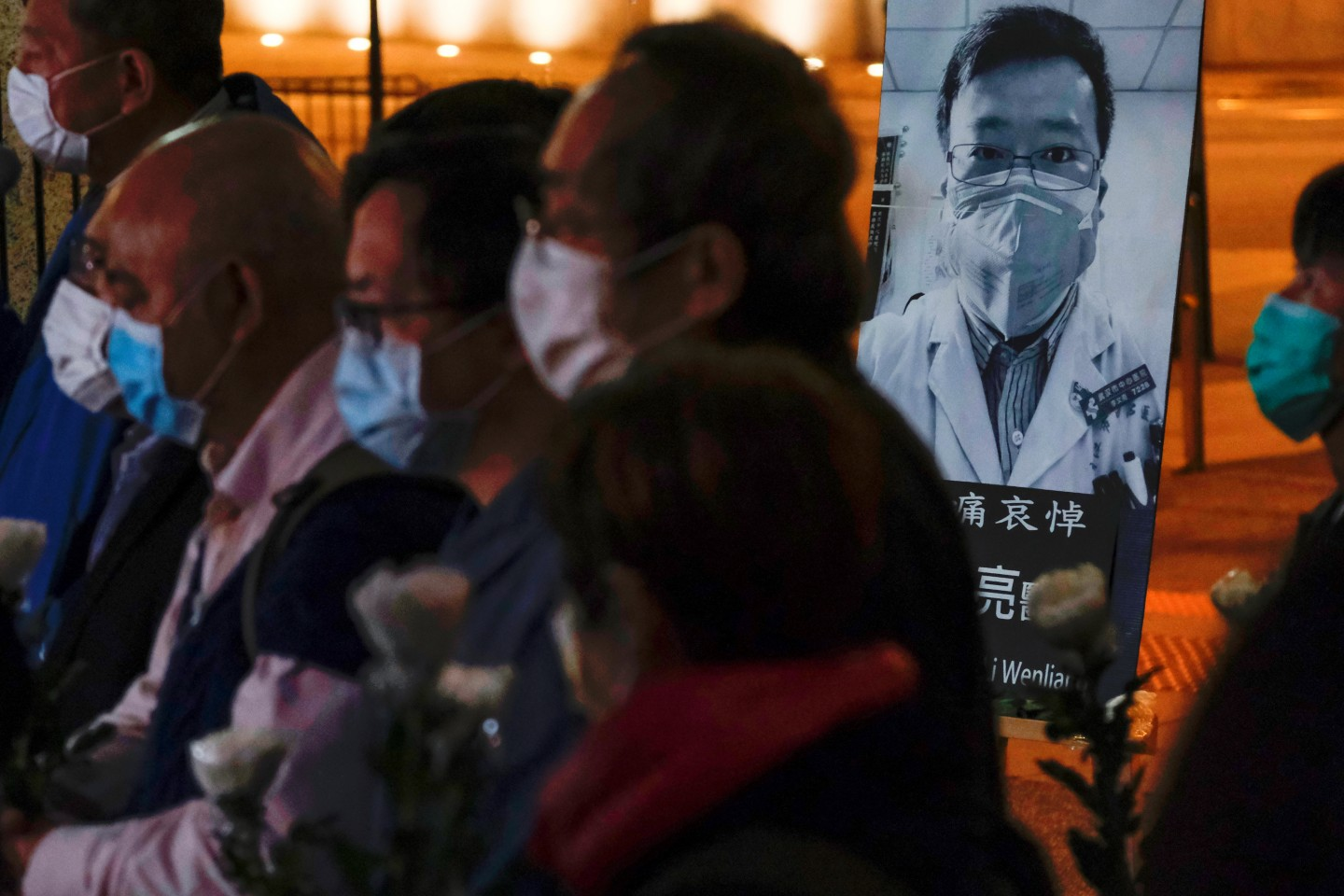 People wearing masks attend a vigil for late Li Wenliang, an ophthalmologist who died of coronavirus at a hospital in Wuhan. (Tyrone Siu/Reuters)