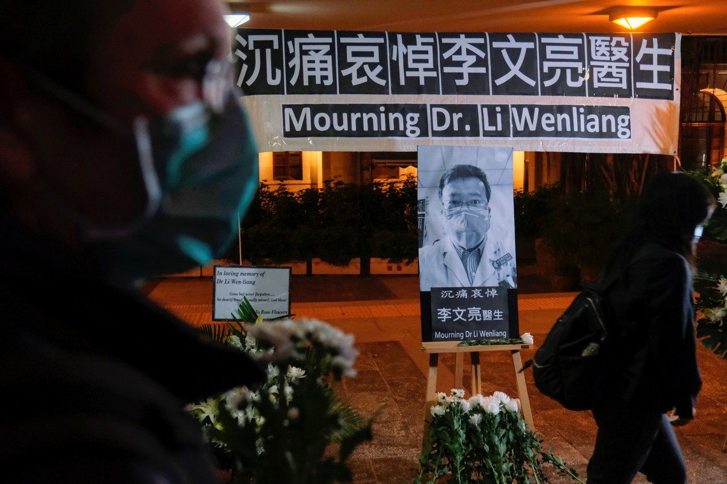 In this photo taken on 7 February 2020, people wearing masks attend a vigil in Hong Kong for late Dr Li Wenliang, an ophthalmologist who died of Covid-19 at a hospital in Wuhan. (Tyrone Siu/Reuters)