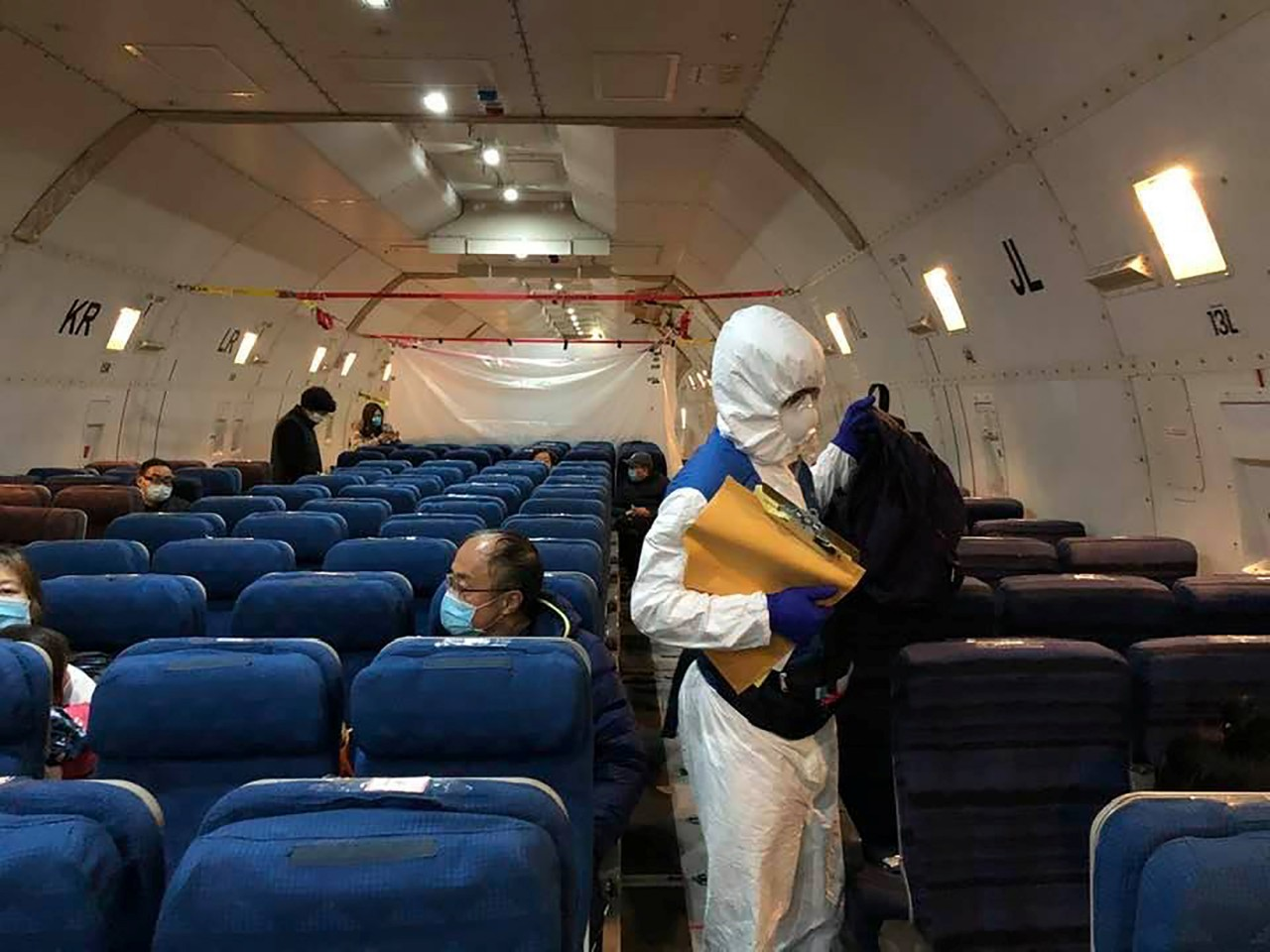 Staff from the US embassy walk in a cargo plane chartered by the US State Department to evacuate Americans and Canadians from China.(Courtesy of Edward Wang via Reuters)