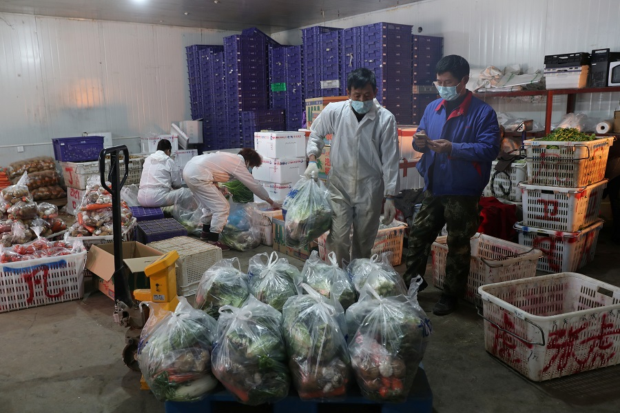 Workers wearing face masks pack vegetables at Baishazhou market in Wuhan, the epicentre of the Covid-19 outbreak, in Hubei province, China on 19 February 2020. (China Daily via REUTERS)