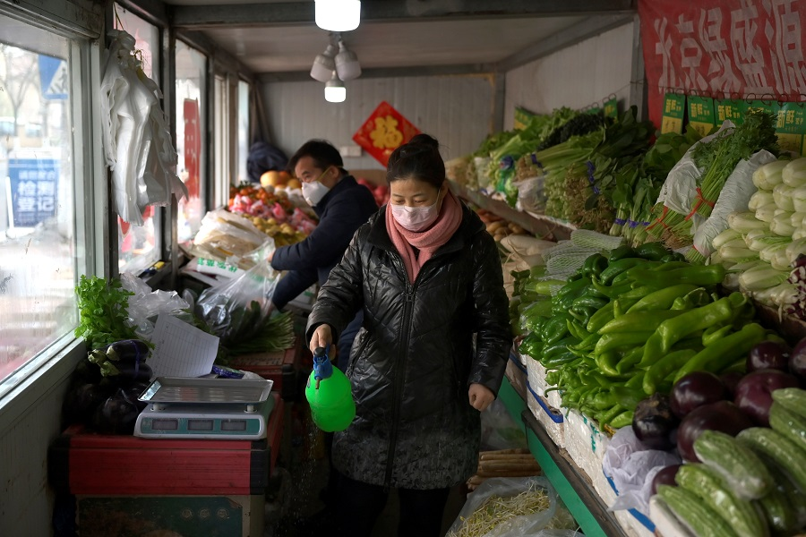 A shop owner disinfects her vegetables shop near a residential compound as the country is hit by an outbreak of the novel coronavirus in Beijing, China on 21 February 2020. (Tingshu Wang/Reuters)