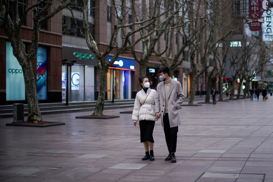 A couple wear masks at a main shopping area in downtown Shanghai, China on 21 February 2020. (Aly Song/Reuters)