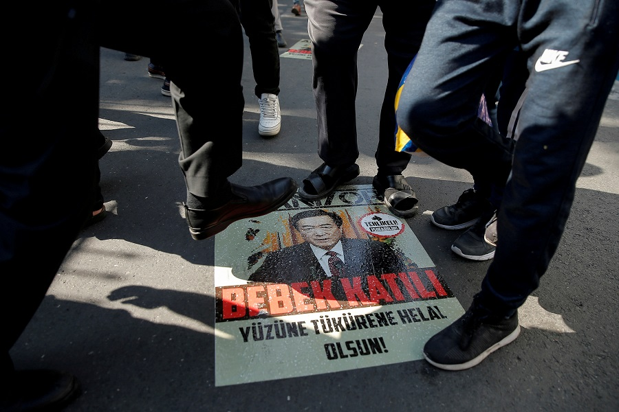 Ethnic Uighur demonstrators step on a poster with an image of Communist Party Secretary of Xinjiang Uighur Autonomous Region Chen Quanguo, during a protest against China in front of the Chinese Consulate in Istanbul, Turkey, on 1 October 2019. (Huseyin Aldemir/File Photo/Reuters)