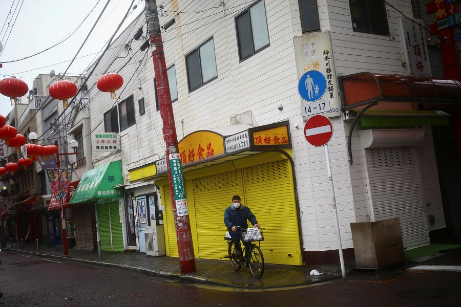 A man wearing protective face mask following an outbreak of the Covid-19 pandemic rides on his bicycle on an almost empty street in Yokohama's Chinatown, Tokyo, Japan on 10 March 2020. (Edgard Garrido/Reuters)