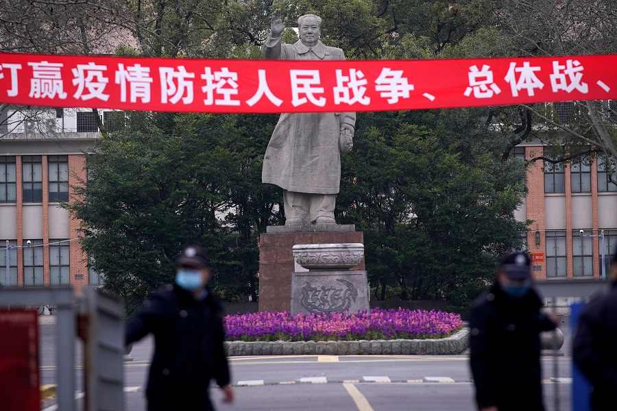 Security guards wearing protective masks are seen in front of a statue of former Chinese leader Mao Zedong at Tongji University amid the Covid-19 pandemic, in Shanghai, China on 12 March 2020. (Aly Song/Reuters)