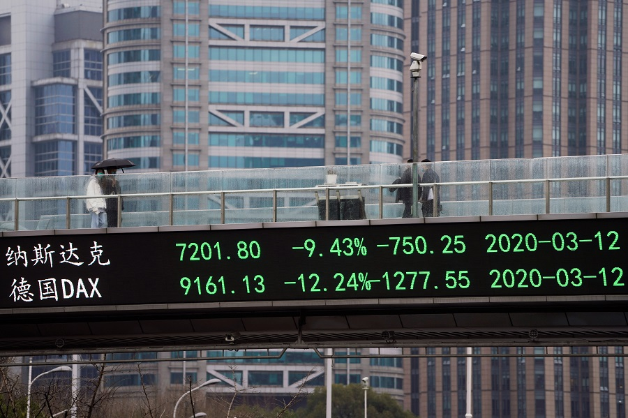 People wearing face masks walk on a pedestrian overpass with an electronic board showing stock indexes, following the Covid-19 outbreak, at Lujiazui financial district in Shanghai, China, on 13 March 2020. (Aly Song/Reuters)