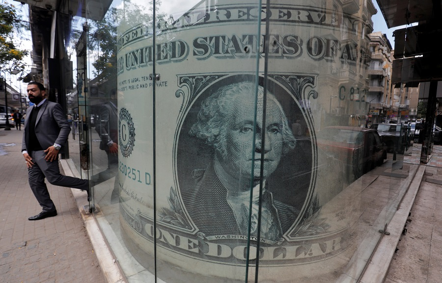 A man leaves a currency exchange bureau showing an image of the US dollar in Cairo, Egypt on 17 March 2020. (Amr Abdallah Dalsh/Reuters)