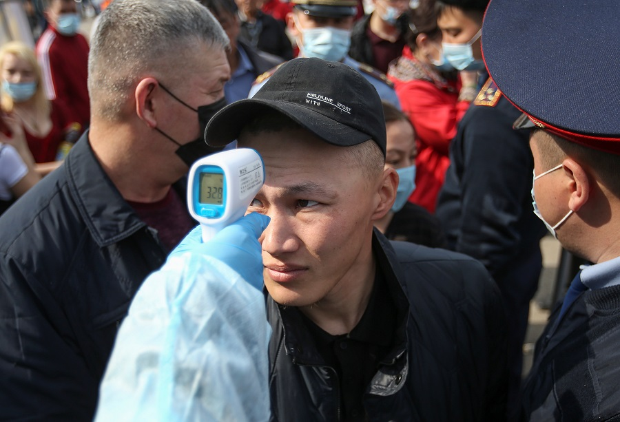 A medical official wearing protective gear takes the body temperature of a man who waits in line to enter the city following the Kazakh state emergency commission's decision to lock down Almaty at a check point on the outskirts of Almaty, Kazakhstan, on 19 March 2020. (Pavel Mikheyev/Reuters)