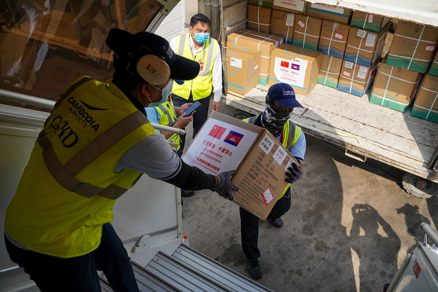 Medical supplies are carried from a plane as a flight arrives from China to Cambodia with supplies and medical staff to contain the spread of the Covid-19 pandemic, at Phnom Penh International Airport in Cambodia, on 23 March 2020. (Cindy Liu/Reuters)
