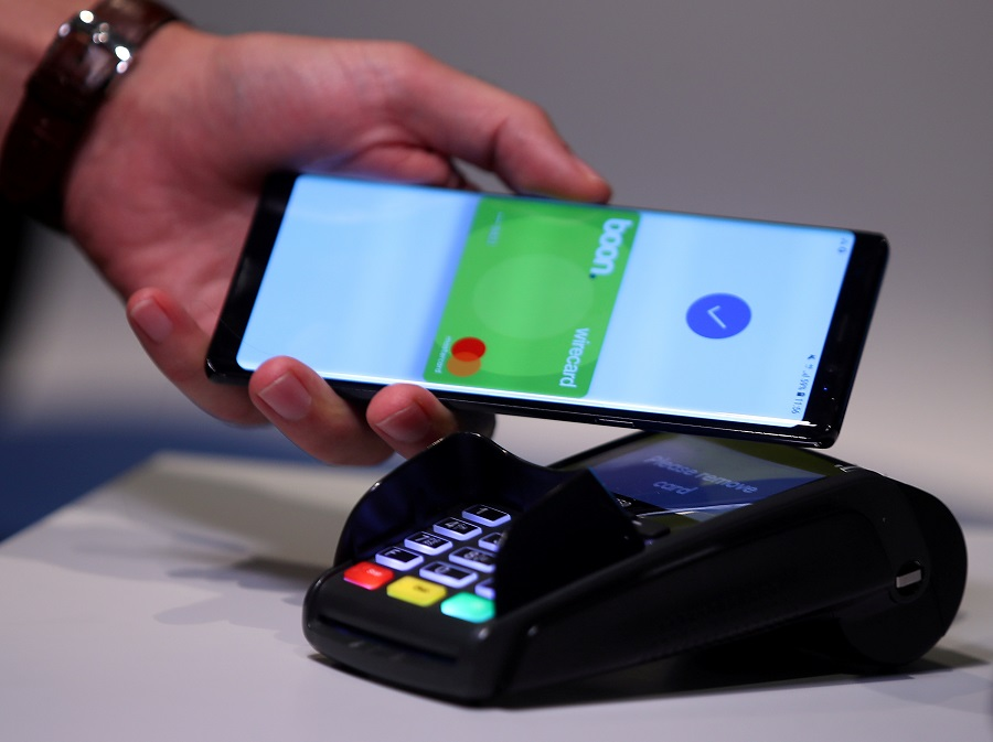 """An employee of Wirecard AG, an independent provider of outsourcing and white label solutions for electronic payment transactions, presents the contactless payment system """"boon"""" at the company's headquarters in Aschheim, Munich, Germany on 6 September 2018. (Michael Dalder/File Photo/Reuters)"""