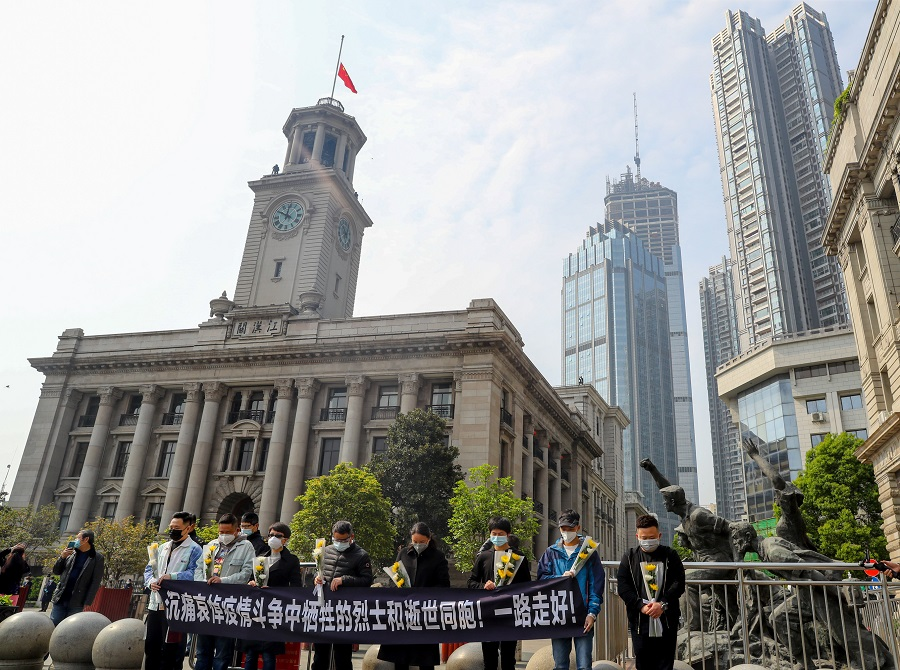 People observe a moment of silence outside Hankou Customs House where the Chinese national flag flies at half mast, in Wuhan, Hubei province, on 4 April 2020. (CNS photo via Reuters)