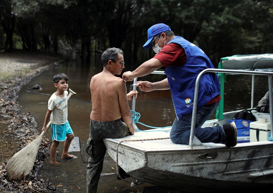 A health agent vaccinates an elderly man against flu and H1N1, as advised by health officials to facilitate diagnosis for coronavirus, amid the Covid-19 outbreak, along the Negro River banks, where the Ribeirinhos live, in Manaus, Brazil, on 2 April 2020. (Bruno Kelly/Reuters)