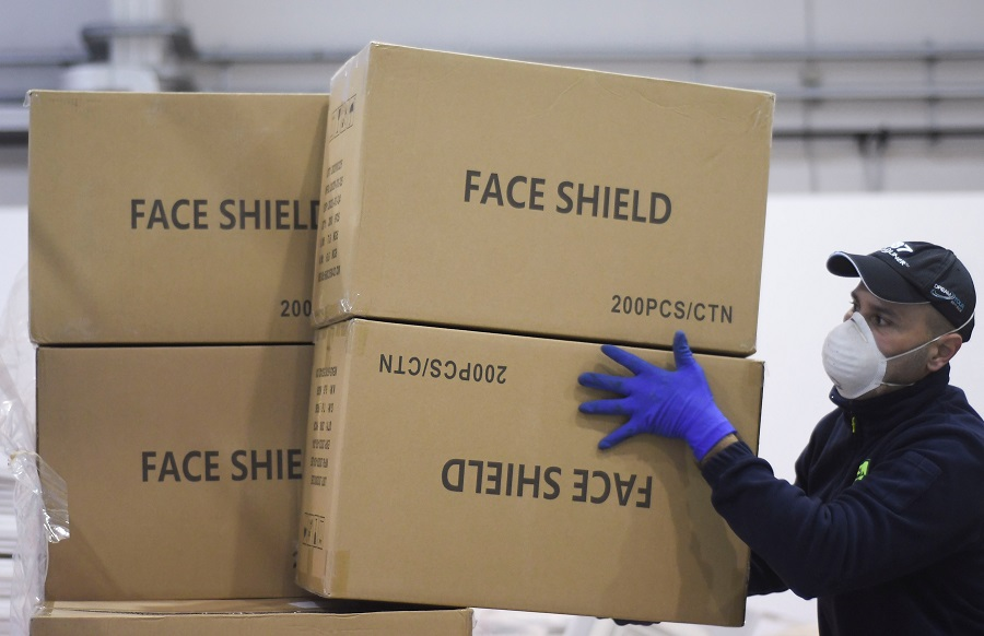 A worker piles up a shipment containing supplies of personal protective equipment at Bari airport after arriving from Guangzhou, China, to help the southern Italian region of Puglia combat the spread of the Covid-19 pandemic, on 7 April 2020. (Alessandro Garofalo/Reuters)