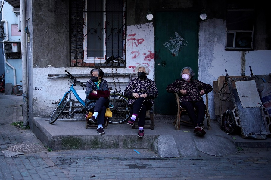 In this photo taken on 12 April 2020, residents wearing face masks are seen at a blocked residential area after the lockdown was lifted in Wuhan, China. (Aly Song/Reuters)