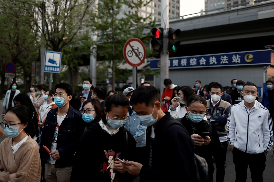 People wearing protective face masks leave work after office hours in Beijing's central business district on 17 April 2020. (Thomas Peter/Reuters)