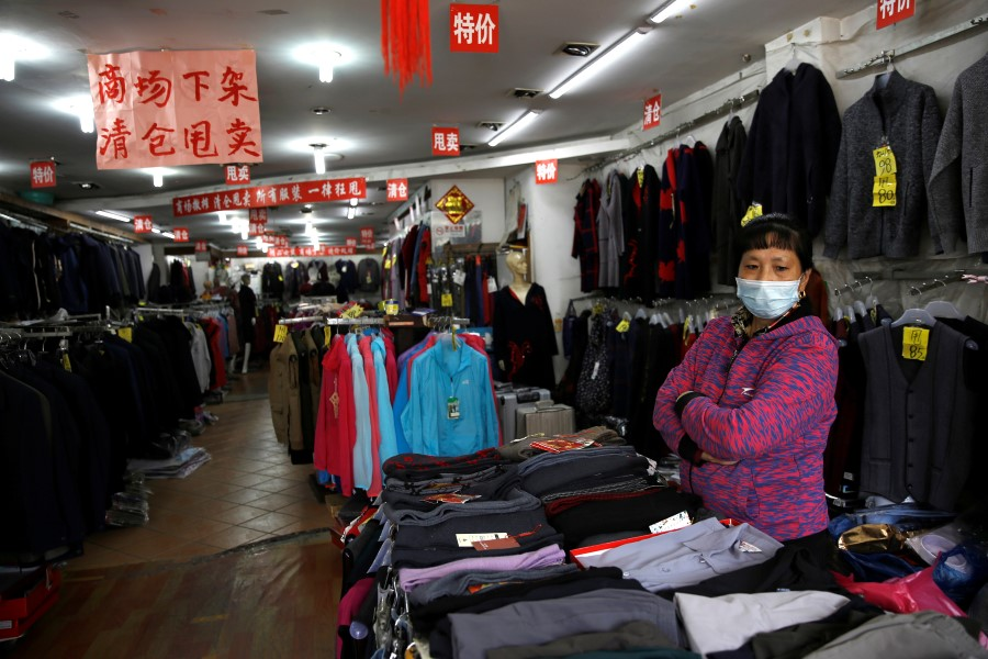 A staff wearing a face mask waits for customers inside a clothing store where business has been struggling since the Covid-19 outbreak, in Beijing, China, on 14 April 2020. (Tingshu Wang/Reuters)