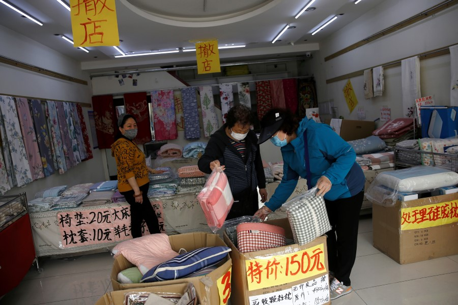 Customers wearing face masks shop bed linen under business closure notices inside a home linen store whose business has been struggling since the Covid-19 outbreak, in Beijing, China, on 14 April 2020. (Tingshu Wang/Reuters)