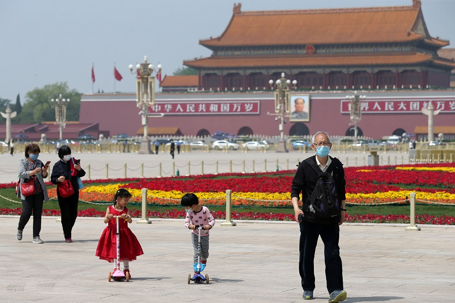 People wearing face masks following the Covid-19 coronavirus outbreak walk past flower installations set up to mark the upcoming Labour Day holiday, at Tiananmen Square in Beijing, China on 29 April 2020. (China Daily via Reuters)