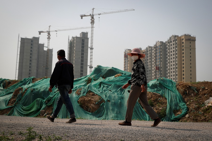 People wear protective masks as they walk past a construction site for residential housing amid the spread of the Covid-19 coronavirus in Beijing, China, on 30 April 2020. (Thomas Peter/Reuters)