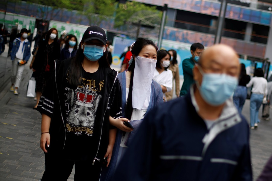 People wearing face masks walk in a shopping district, amid the Covid-19 outbreak, in Beijing, China on 4 May 2020. (Thomas Peter/Reuters)
