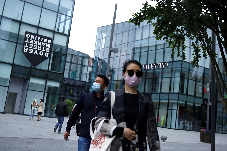 People wearing face masks shop at the Sanlitun shopping area in Beijing, China, on 4 May 2020. (Tingshu Wang/Reuters)