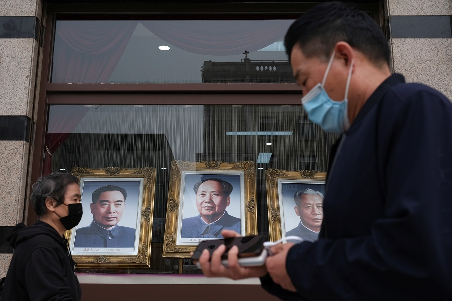 People wearing face masks walk past portraits of late Chinese Communist Party leaders (left to right) Zhou Enlai, Mao Zedong and Liu Shaoqi, in Beijing, China on 7 May 2020. (Carlos Garcia Rawlins/Reuters)