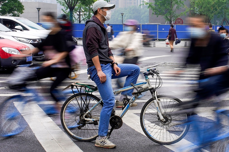 People wearing protective face masks ride bicycles on a street in Wuhan, China, on 14 May 2020. (Aly Song/Reuters)