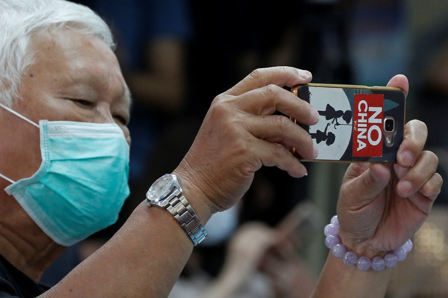 "A man with a ""No China"" sticker on his phone is seen at a press conference pertaining to Taiwan's efforts to get into the World Health Organization in Taipei, Taiwan, on 15 May 2020. (Ann Wang/Reuters)"