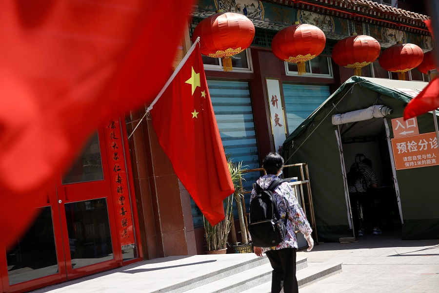 A woman walks outside a traditional Chinese medicine hospital decorated with a Chinese flag following the coronavirus outbreak, in Beijing, China on 19 May 2020. (Tingshu Wang/Reuters)