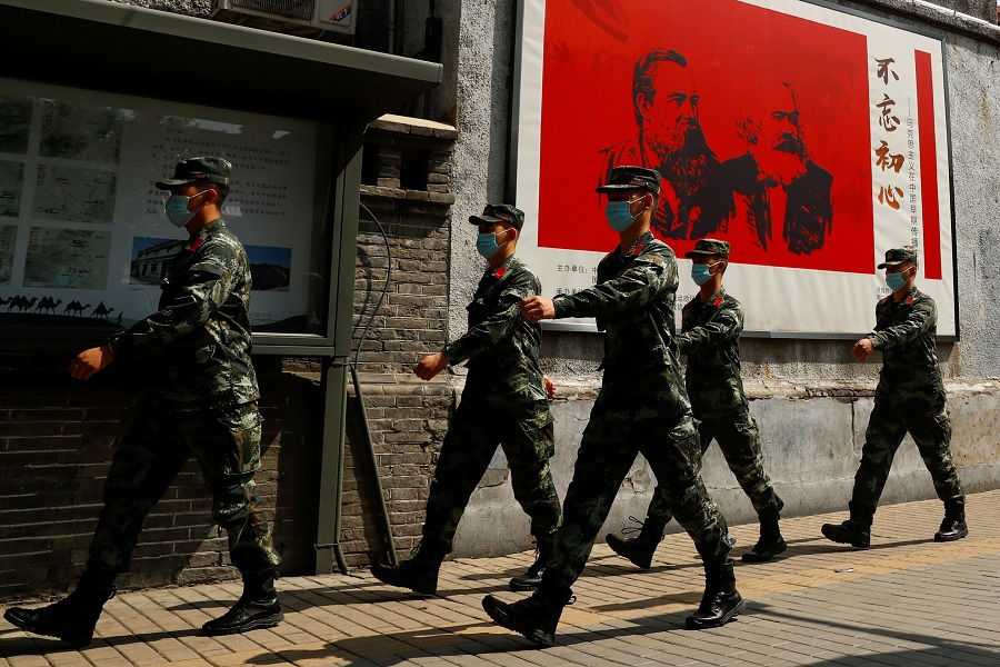 "Chinese servicemen walk past portraits of philosophers Karl Marx and Friedrich Engels with the caption ""Remain True to our Original Aspiration"" (不忘初心) and patrol a street near the Great Hall of the People on the opening day of the National People's Congress, in Beijing, China, on 22 May 2020. (Thomas Peter/Reuters)"